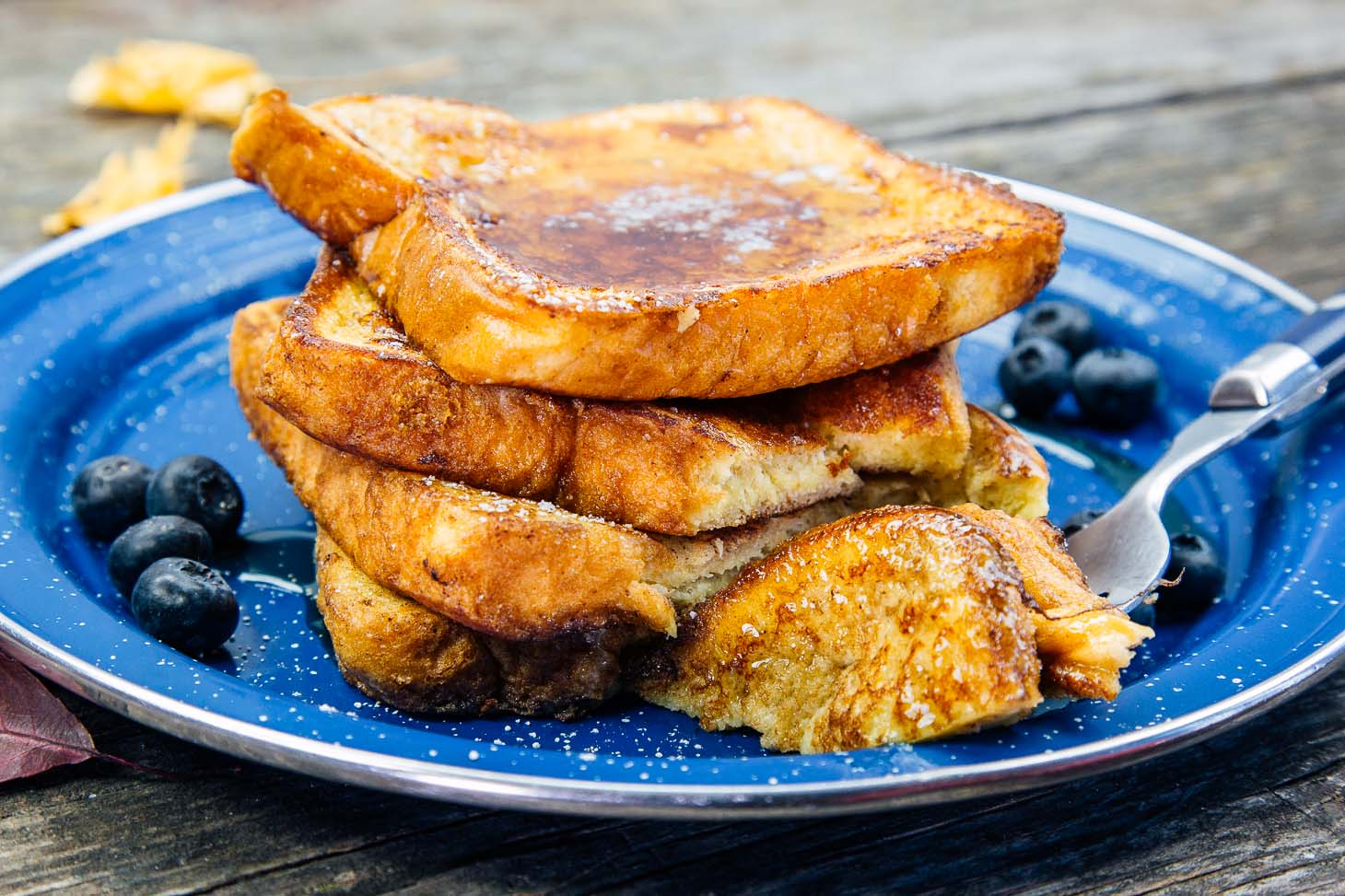 A stack of pumpkin spiced french toast on a blue enamel camping plate.
