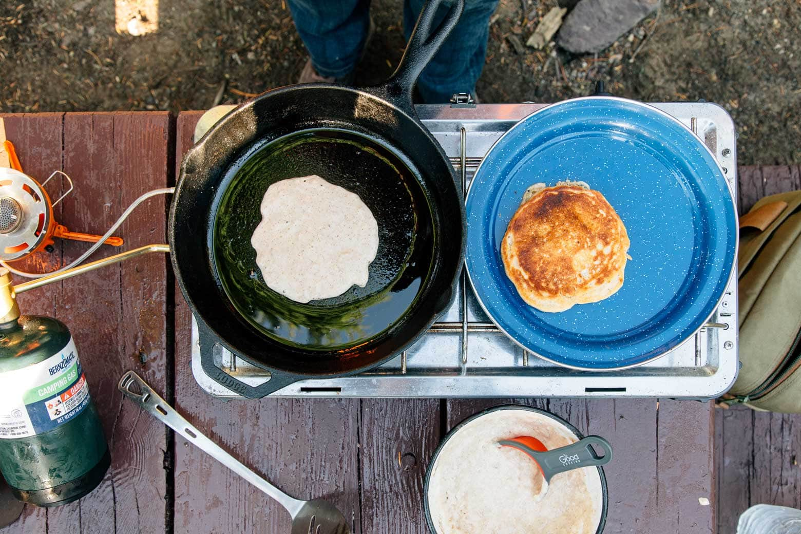 Cooking pancakes in a skillet on a camping stove
