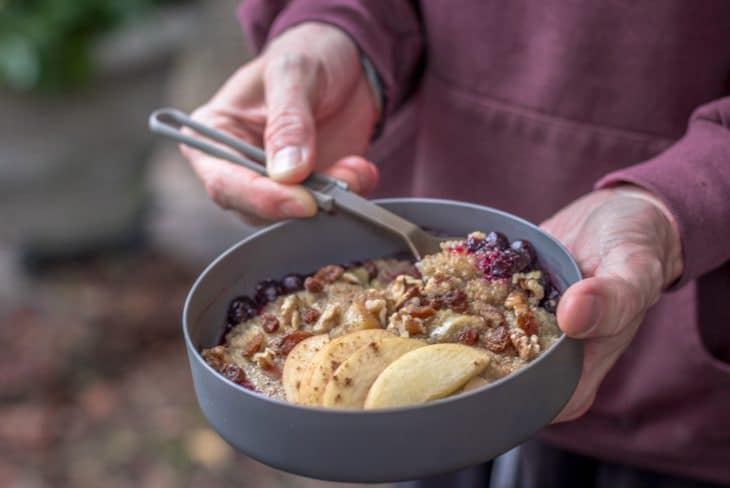 Holding a bowl of breakfast quinoa porridge with apples.
