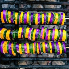 Three kabobs with sliced eggplant, zucchini, and yellow squash on a grill