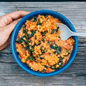 Lentil stew and kale in a blue bowl with hands in frame
