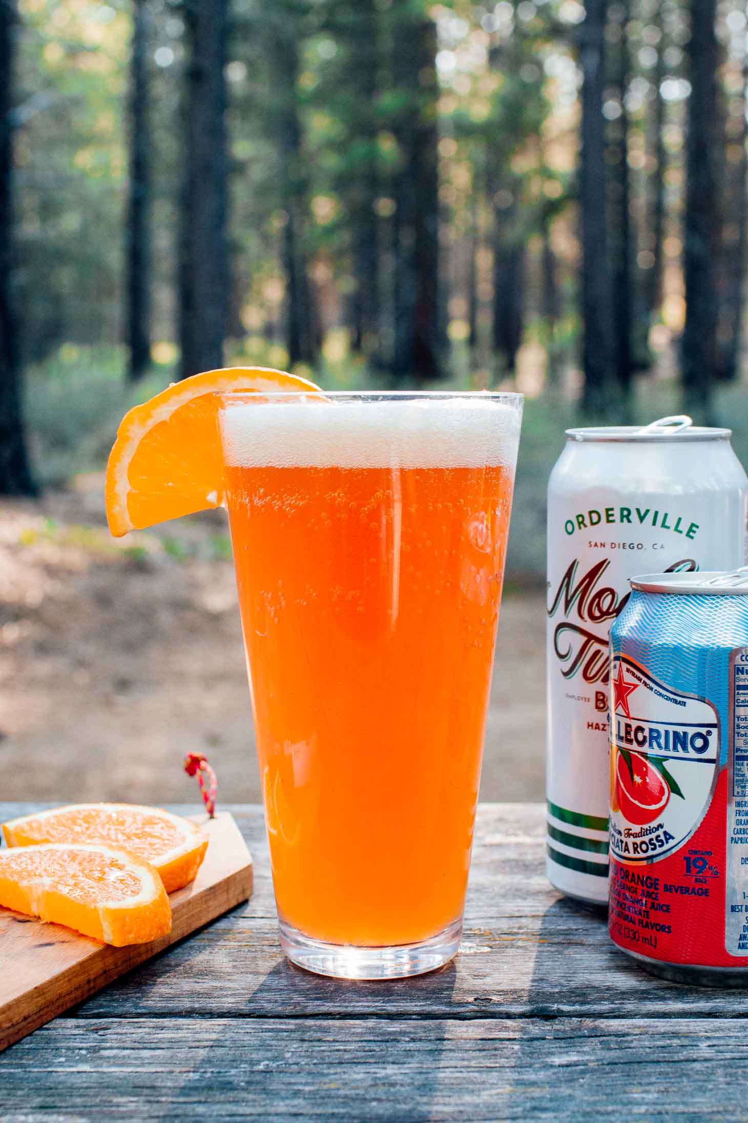 A shandy and ingredients with a forest scene in the background
