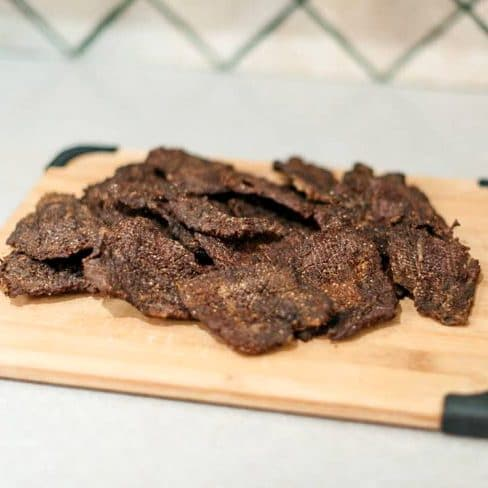 A pile of beef jerky on a wood cutting board.