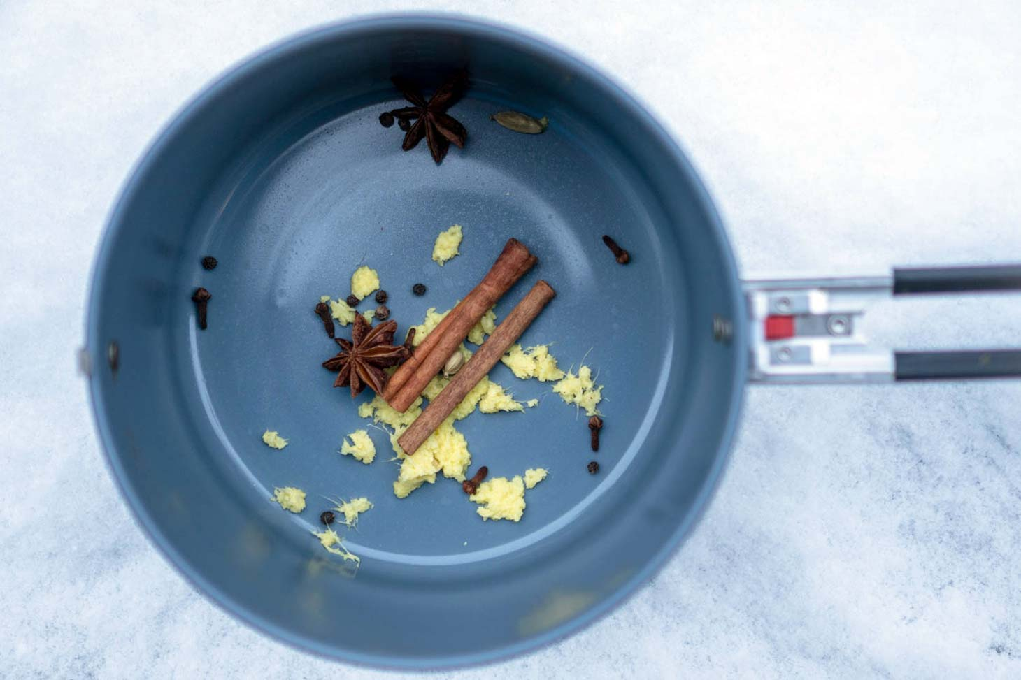 Ginger, cinnamon sticks, cloves, and star anise in a pot
