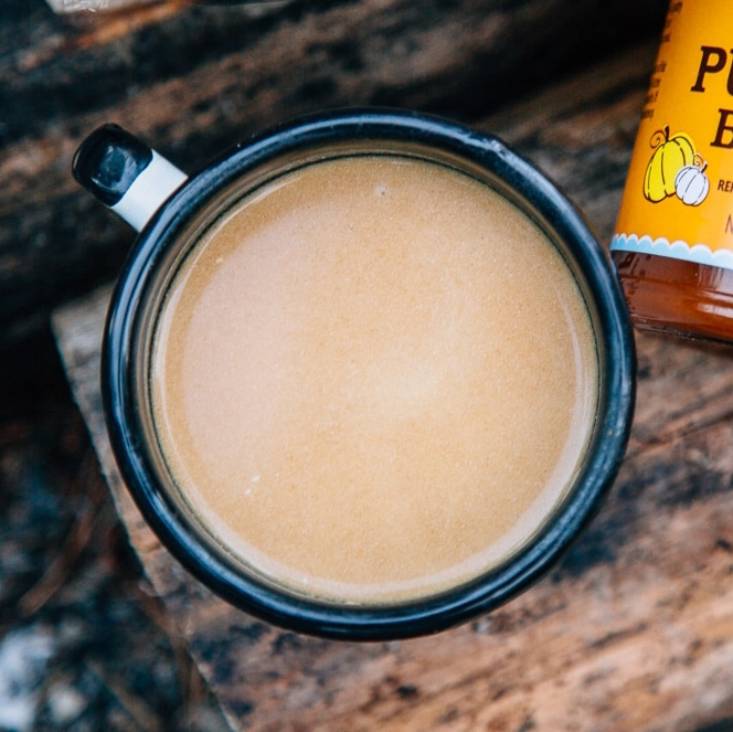 Pumpkin chai in a mug on a wood log