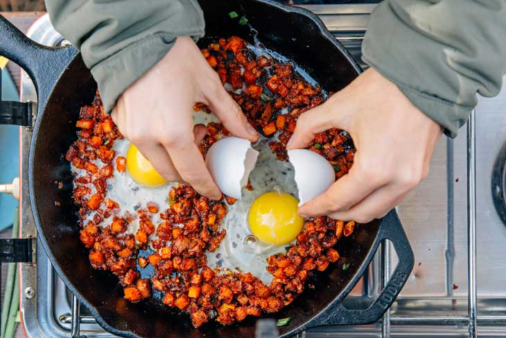 Cracking eggs into a camping skillet for breakfast hash
