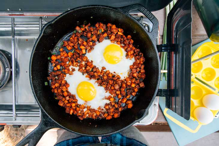 Sunny side up eggs in a camping skillet with sweet potato hash