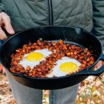 Woman holding a cast iron skillet with eggs and sweet potato hash.