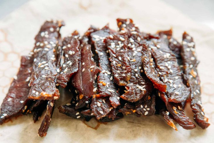 Side view of teriyaki beef jerky stacked on a napkin.