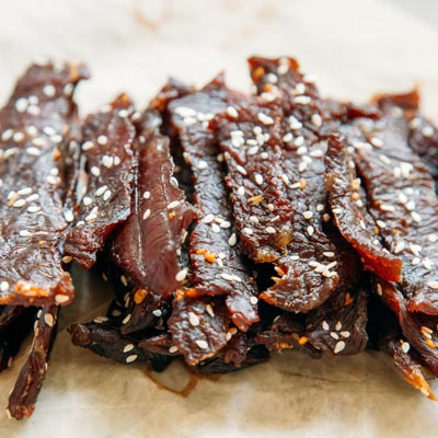 A pile of beef jerky with sesame seeds