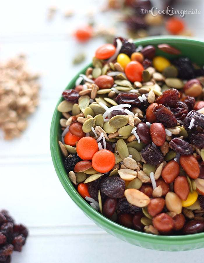 Nut, seed, raisins, and candy pieces in a green bowl