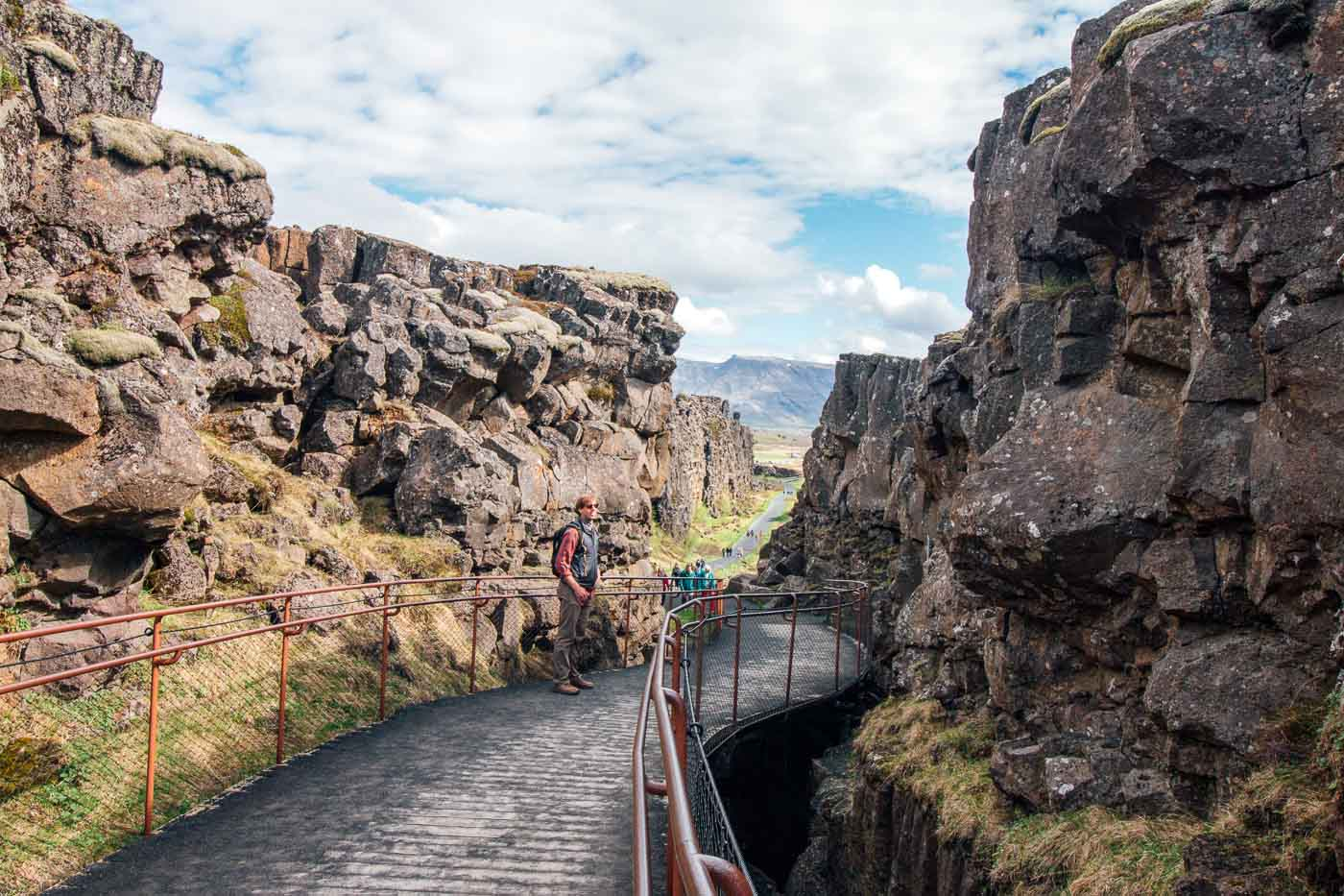 Michael walking on a pathway between rock formations at Thingvellir
