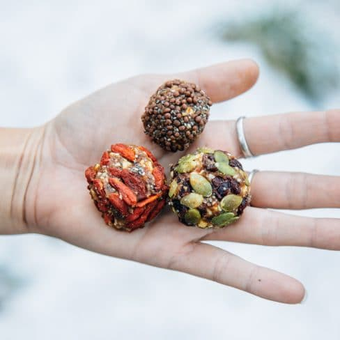 Hand holding three energy bites with a snowy background