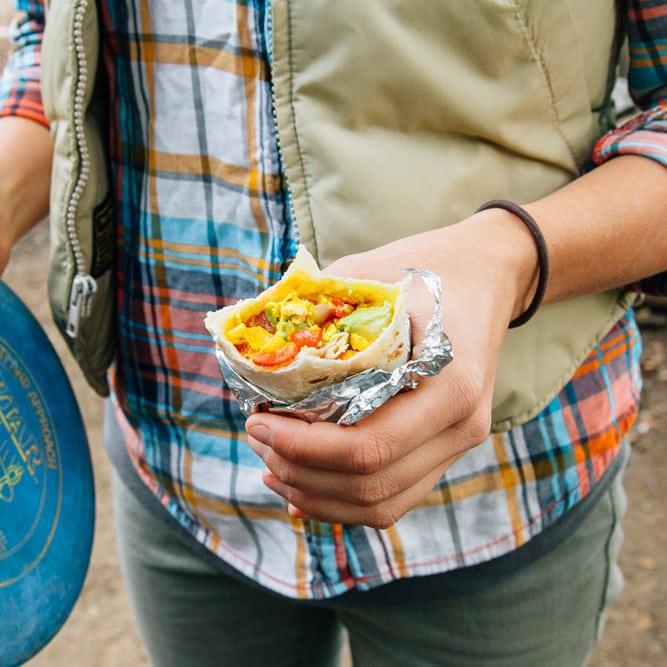Megan holding a tofu scramble breakfast burrito