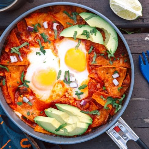 A skillet with chilaquiles, two eggs, and sliced avocado